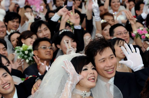 Newly wed couples pose for photos during a mass wedding ceremony organized by Taipei city government on September 9, 2010.  More than 160 couples and hundreds of their relatives took part in the ceremony.  AFP PHOTO / Sam YEH