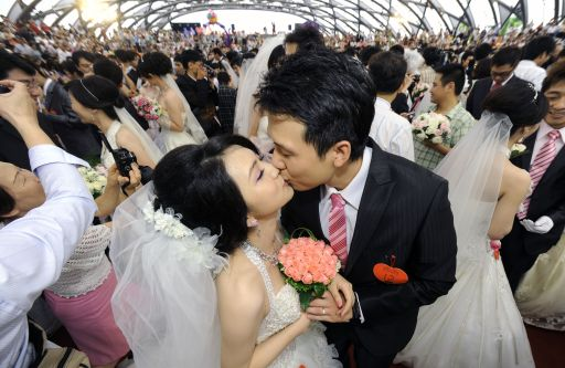 Newly wed couples kiss during a mass wedding ceremony organized by Taipei city government on September 9, 2010.  More than 160 couples and hundreds of their relatives took part in the ceremony.  AFP PHOTO / Sam YEH