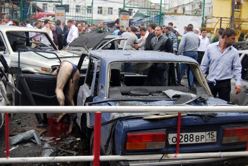 Russian investigators examine the site of a blast near a market in Vladikavkaz on September 9, 2010. At least 15 people were killed on and dozens wounded in an apparent suicide bombing outside a crowded central market in the Russian Caucasus city of Vladikavkaz, officials said. AFP PHOTO / STR