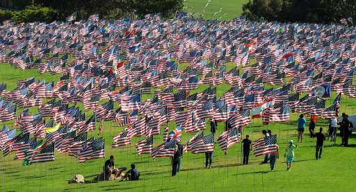 "Americans walk amongst flags erected by students and staff from Pepperdine University in Malibu, who placed nearly 3000 flags in the ground to honor the victims of the September 11, 2001 terrorist attacks in New York, on September 10, 2010.   An impassioned President Barack Obama warned Americans must not turn on one another over religion, after rows over Islam sparked global fury, nine years after the September 11 attacks. Obama also mounted a strident defense of American Muslims, paid tribute to believers fighting in the US armed forces, and said US citizens must remember who their true enemies were -- naming Al-Qaeda and ""terrorists."" The President has vowed a ""new beginning"" with Islam, but international tensions have spiked over a plan for a Muslim cultural center near the felled World Trade Center site in New York and a US pastor's threat to burn Korans.           AFP PHOTO/Mark RALSTON"