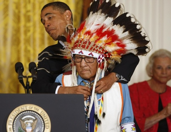 U.S. President Barack Obama reacts as he dodges a feather on the head dress of Joe Medicine Crow, as he presents the Medal of Freedom during a ceremony in the East Room of the White House in Washington August 12, 2009. Obama presented the nation's highest civilian honour to 16 recipients during the ceremony. REUTERS/Jason Reed (UNITED STATES POLITICS SOCIETY)