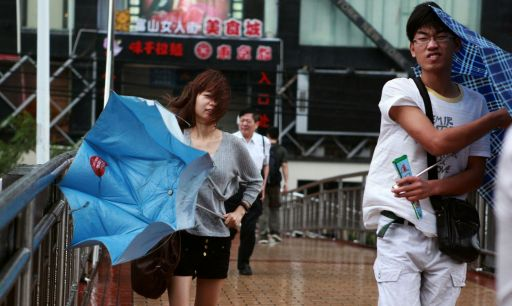 Pedestrians use their umbrellas to shield from strong winds and rain as Typhoon Fanapi makes landfall along the coast in Xiamen, in southeast China's Fujian province on September 20, 2010. China warned of flash floods and landslides as Typhoon Fanapi made landfall on the mainland one day after slamming Taiwan with heavy rains, leaving more than 100 injured on the island.  CHINA OUT   AFP PHOTO