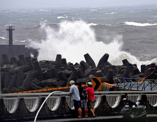 Local residents watch a large wave hit the coast along Nanfangauo harbour in Yilan county, eastern Taiwan, as the island braces itself for Typhoon Fanapi on September 19, 2010. Taiwan was lashed by winds of almost 200 kilometres an hour as the most powerful typhoon of the year smashed into the island, just a year after a devastating storm left hundreds dead.   AFP PHOTO / PATRICK LIN