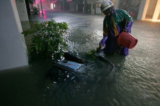 A man tries to remove his motorbike from flood water in southern Kaohsiung city as typhoon Fanapi hits east Taiwan on September 19, 2010. Taiwan was pounded by winds of more than 200 km per hour as China evacuated 150,000 people, issuing an alert over what could be the fiercest typhoon of the year to hit the region.  AFP PHOTO / STR