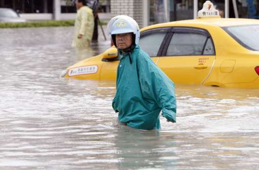 TAIWAN OUT A man walks past a taxi trapped in flood waters in the southern Taiwan city of Kaohsiung on September 20, 2010 after Typhoon Fanapi crossed the island the day before dumping up to a metre of water of rain in some places.  Schools and offices were closed in typhoon-hit parts of Taiwan as residents started clearing up after their homes were flooded by the storm.   TAIWAN OUT     AFP PHOTO