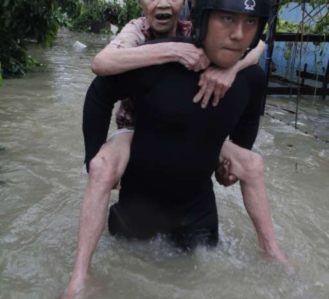 TAIWAN OUT A rescurer carries a woman through flood waters in the southern Taiwan city of Kaohsiung on September 20, 2010 after Typhoon Fanapi crossed the island the day before dumping up to a metre of water of rain in some places.  Schools and offices were closed in typhoon-hit parts of Taiwan as residents started clearing up after their homes were flooded by the storm.   TAIWAN OUT     AFP PHOTO
