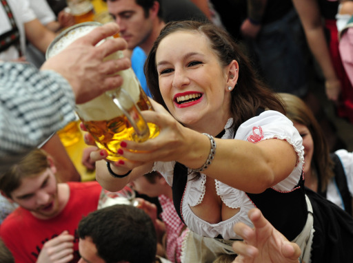 "A young woman wearing a traditiional Bavarian ""Dirndl"" dress smlies as she receives a mug of beer in the Hofbraeuhaus-tent after the opening of the Oktoberfest beer festival  at the Theresienwiese in Munich, southern Germany, on September 18, 2010. The world's biggest beer festival will last until October 4, 2010.  AFP PHOTO / THOMAS KIENZLE"