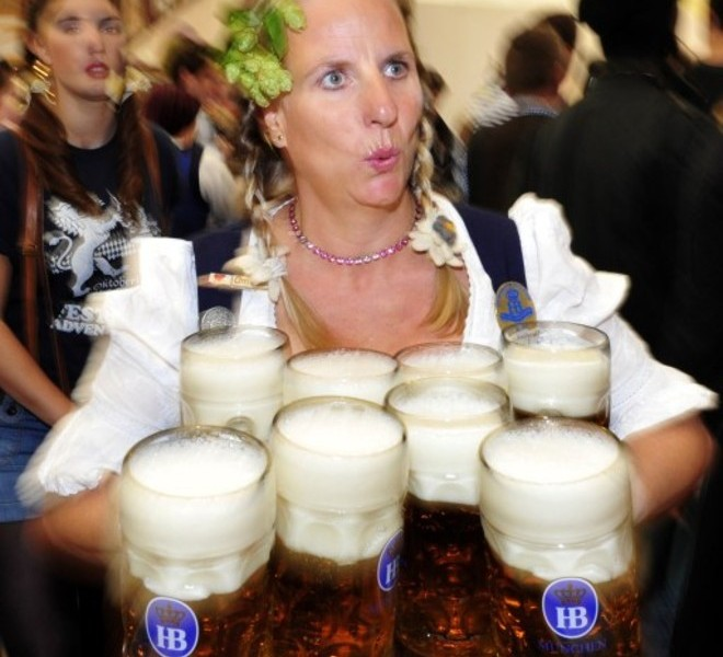 "A waitress wearing a traditional Bavarian ""Dirndl"" dress smlies as she carries mugs of beer in the Hofbraeuhaus-tent after the opening of the Oktoberfest beer festival  at the Theresienwiese in Munich, southern Germany, on September 18, 2010. The world's biggest beer festival will last until October 4, 2010.  AFP PHOTO / THOMAS KIENZLE"