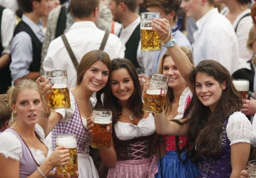 "Young women wearing traditional Bavarian ""Dirndl"" dresses cheer with beer mugs after the official opening of the 177th edition of the Oktoberfest beer festival in a tent at the Theresienwiese in Munich, southern Germany, on September 18, 2010. The world's biggest beer festival Oktoberfest, celebrating the 200th birthday since its creation, runs until October 4, 2010.   AFP PHOTO / SEBASTIAN WIDMANN"