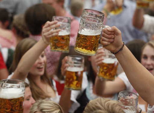 Visitors cheer with beer mugs after the official opening of the 177th edition of the Oktoberfest beer festival in a tent at the Theresienwiese in Munich, southern Germany, on September 18, 2010. The world's biggest beer festival Oktoberfest, celebrating the 200th birthday since its creation, runs until October 4, 2010.   AFP PHOTO / SEBASTIAN WIDMANN