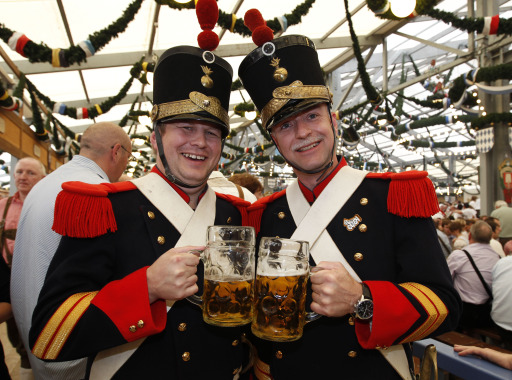 Two visitors from Basel, Switzerland, wearing traditional Basel city guard uniforms, cheer with beer mugs in a tent on the opening day of the 177th edition of the Oktoberfest beer festival at the Theresienwiese in Munich, southern Germany, on September 18, 2010. The world's biggest beer festival Oktoberfest, celebrating the 200th birthday since its creation, runs until October 4, 2010.   AFP PHOTO / SEBASTIAN WIDMANN