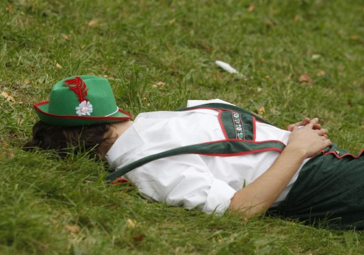 A drunken visitor sleeps on a lawn on the opening day of the 177th edition of the Oktoberfest beer festival at the Theresienwiese in Munich, southern Germany, on September 18, 2010. The world's biggest beer festival Oktoberfest, celebrating the 200th birthday since its creation, runs until October 4, 2010.   AFP PHOTO / SEBASTIAN WIDMANN