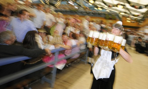 "A waitress wearing a traditional Bavarian ""Dirndl"" dress carries beer mugs after the official opening of the 177th edition of the Oktoberfest beer festival in a tent at the Theresienwiese in Munich, southern Germany, on September 18, 2010. The world's biggest beer festival Oktoberfest, celebrating the 200th birthday since its creation, runs until October 4, 2010.   AFP PHOTO / CHRISTOF STACHE"