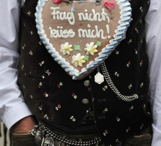 "A man in the traditional Bavarian clothes wears a gingerbread-heart reading ""Don't ask, kiss me!"" at the opening of the Oktoberfest beer festival at the Theresienwiese in Munich, southern Germany, on September 18, 2010. The world's biggest beer festival will run until October 4, 2010.  AFP PHOTO / THOMAS KIENZLE"