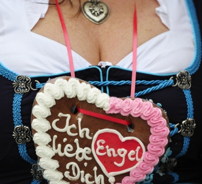 "A woman in traditional Bavarian clothes, wears a gingerbread-heart reading ""I love you Angel"" around her neck at the opening of the Oktoberfest beer festival  #at the Theresienwiese in Munich, southern Germany, on September 18, 2010. The world's biggest beer festival will run until October 4, 2010.  AFP PHOTO / THOMAS KIENZLE"
