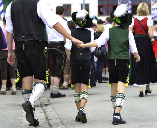 Two boys wearing traditional Bavarian clothes walk with their father over the fair-ground on the opening day of the Oktoberfest beer festival  at the Theresienwiese in Munich, southern Germany, on September 18, 2010. The world's biggest beer festival will last until October 4, 2010.  AFP PHOTO / THOMAS KIENZLE