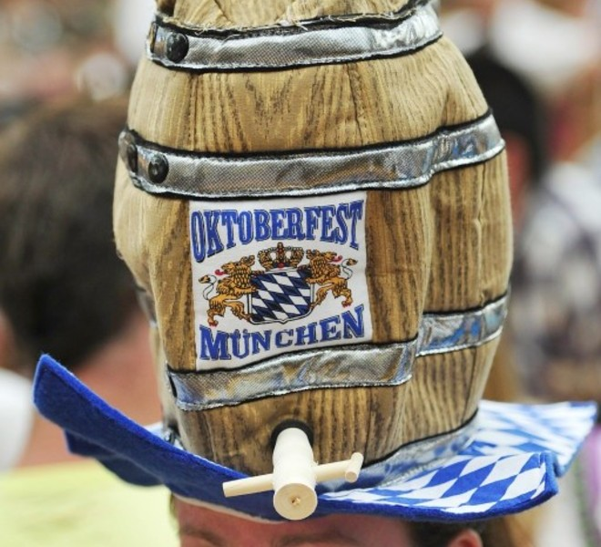 "A young woman wears a hat featuring a beer barrel with a logo reading ""Oktoberfest Muenchen"" after the opening of the Oktoberfest beer festival  at the Theresienwiese in Munich, southern Germany, on September 18, 2010. The world's biggest beer festival will last until October 4, 2010.  AFP PHOTO / THOMAS KIENZLE"