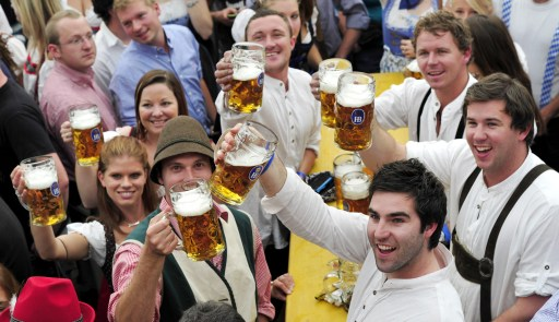 Visitors in traditional Bavarian clothes enjoy cheer with beers mugs in the Hofbraeuhaus tent after the opening of the Oktoberfest beer festival  at the Theresienwiese in Munich, southern Germany, on September 18, 2010. The world's biggest beer festival will last until October 4, 2010.  AFP PHOTO / THOMAS KIENZLE