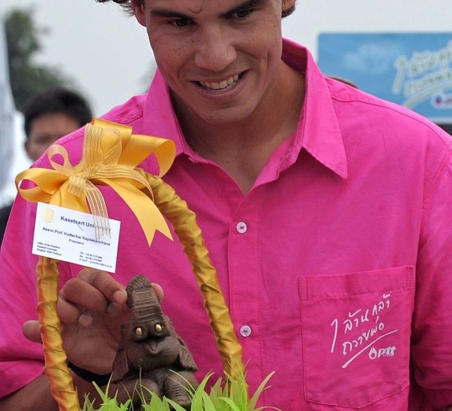 "World number one men's tennis player Rafael Nadal holds a souvenir as he takes part in a tree planting project in honour of Thai King Bhumibol Adulyadej's ""One Million Trees for the King"" during a visit to the Thai city of Hua Hin on September 28, 2010. Nadal will compete in the ATP Thailand Open tennis tournament starting on September 27.    AFP PHOTO / PORNCHAI KITTIWONGSAKUL"