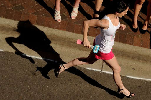 "A competitor runs during a heat of the ""Venus Embrace Closest Stiletto Relay"" in Sydney on September 28, 2010.  An official world record was set at the event for the fastest ever 4 x 100m stiletto relay, which saw women in teams of four running in stilettos with a minimum height of 3 inches, to help raise funds to find a cure for breast cancer. AFP PHOTO / Greg WOOD"