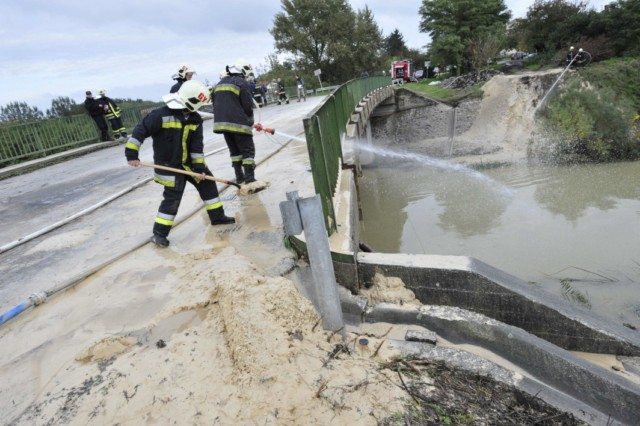 Firemen of the Gyor town station wash a special material, industrial gypsum into the Marcal River to coagulate the toxic water at Morichida village about 150 kms west from Budapest on October 6, 2010. Several dozen family houses were flooded by the red-sludge from an alumina plant in western Hungary on Monday, flooding several towns, villages with towering waves of red sludge. Five people died, seven were missing and hundreds were injured, rescue services said. The spill of an estimated 1,000,000 cubic metres of sludge affected several localities such as Kolontar and Devecser near the Ajkai Timfoldgyar plant in the town of Ajka. AFP PHOTO / ATTILA KISBENEDEK