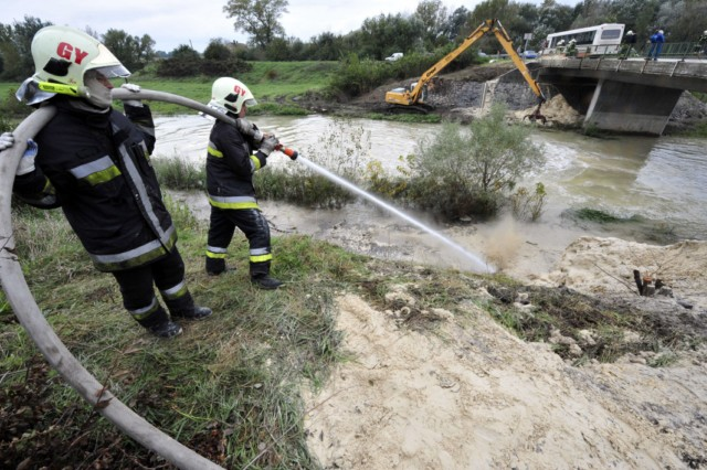 "Firemen of the Gyor town station wash a special material, industrial gypsum into the Marcal River to coagulate the toxic water at Morichida village about 150 kms west from Budapest on October 6, 2010. Several dozen family houses were flooded by the red-sludge from an alumina plant in western Hungary on Monday, flooding several towns, villages with towering waves of red sludge. Five people died, seven were missing and hundreds were injured, rescue services said. The spill of an estimated 1,000,000 cubic metres of sludge affected several localities such as Kolontar and Devecser near the Ajkai Timfoldgyar plant in the town of Ajka. AFP PHOTO / ATTILA KISBENEDEK , Firemen of the Gyor town station wash a special material, industrial gypsum, into the Marcal River to coagulate the toxic water at Morichida village about 150 kms west from Budapest on October 6, 2010. Several dozen family houses were flooded by the red-sludge from an alumina plant in western Hungary on Monday, flooding several towns, villages with towering waves of red sludge. Five people died, seven were missing and hundreds were injured, rescue services said. The spill of an estimated 1,000,000 cubic metres of sludge affected several localities such as Kolontar and Devecser near the Ajkai Timfoldgyar plant in the town of Ajka. AFP PHOTO / ATTILA KISBENEDEK , An excavator pours industrial gypsum to reduce the alkalinity into the Marcal River at the bridge of Szente about 150 kms west from Budapest on October 6, 2010. Several dozen family houses were flooded by the red-sludge from an alumina plant in western Hungary on Monday, flooding several towns, villages with towering waves of red sludge. Four people died, seven were missing and hundreds were injured, rescue services said. The spill of an estimated 1,000,000 cubic metres of sludge affected several localities such as Kolontar and Devecser near the Ajkai Timfoldgyar plant in the town of Ajka. AFP PHOTO / ATTILA KISBENEDEK , Dead fish float on the Marcal River at the bridge of Morichida about 150 kms west from Budapest on October 6, 2010. Several dozen family houses were flooded by the red-sludge from an alumina plant in western Hungary on Monday, flooding several towns, villages with towering waves of red sludge.  Four people died, seven were missing and hundreds were injured, rescue services said. The spill of an estimated 1,000,000 cubic metres of sludge affected several localities such as Kolontar and Devecser near the Ajkai Timfoldgyar plant in the town of Ajka. AFP PHOTO / ATTILA KISBENEDEK , White froth floats on the surface of the Raba River as it moves through the town of Gyor, some 130kms from Budapest on October 7, 2010. Hungary's toxic sludge spill, which has killed four people, reached the Danube river on October 7, 2010, threatening to contaminate the waterway's ecosystem, a water authority official told AFP. AFP PHOTO / ATTILA KISBENEDEK , A man walks in sludge mixed with stones in Kolontar about 160 kms southwest of  Budapest, on October 6, 2010 after a wave of toxic red mud swept through the small village two days ago, killing four and injuring scores more. The accident -- which officials say is Hungary's worst-ever chemical accident and an ""ecological disaster"" -- occurred on October 4 when the walls of a reservoir of residue at an aluminium plant in nearby Ajka broke, sending a wave of stinking red sludge through seven villages in the west of the country and leaving a trail of devastation across an area of 40 square kms (15.4 square miles). In Kolontar, the army had to build a temporary bridge to replace one that was swept away by the flood.    AFP PHOTO / ATTILA KISBENEDEK , Civil Protection Service workers clean sludge-covered streets in Kolontar about 160 kms southwest of Budapest, on October 6, 2010 after a wave of toxic red mud swept through the small village two days ago, killing four and injuring scores more. The accident -- which officials say is Hungary's worst-ever chemical accident and an ""ecological disaster"" -- occurred on October 4 when the walls of a reservoir of residue at an aluminium plant in nearby Ajka broke, sending a wave of stinking red sludge through seven villages in the west of the country and leaving a trail of devastation across an area of 40 square kms (15.4 square miles). In Kolontar, the army had to build a temporary bridge to replace one that was swept away by the flood.    AFP PHOTO / ATTILA KISBENEDEK , A man checks bedclothes and pillows in the debris of his flooded house in Kolontar about 160 kms southwest of  Budapest, on October 6, 2010 after a wave of toxic red mud swept through the small village two days ago, killing four and injuring scores more. The accident -- which officials say is Hungary's worst-ever chemical accident and an ""ecological disaster"" -- occurred on October 4 when the walls of a reservoir of residue at an aluminium plant in nearby Ajka broke, sending a wave of stinking red sludge through seven villages in the west of the country and leaving a trail of devastation across an area of 40 square kms (15.4 square miles). In Kolontar, the army had to build a temporary bridge to replace one that was swept away by the flood.    AFP PHOTO / ATTILA KISBENEDEK , A resident cleans his yard in Kolontar about 160 kms southwest of  Budapest, on October 6, 2010 after a wave of toxic red mud swept through the small village two days ago, killing four and injuring scores more. The accident -- which officials say is Hungary's worst-ever chemical accident and an ""ecological disaster"" -- occurred on October 4 when the walls of a reservoir of residue at an aluminium plant in nearby Ajka broke, sending a wave of stinking red sludge through seven villages in the west of the country and leaving a trail of devastation across an area of 40 square kms (15.4 square miles). In Kolontar, the army had to build a temporary bridge to replace one that was swept away by the flood.    AFP PHOTO / ATTILA KISBENEDEK , People remove mud from their garden in the flooded village of Kolontar, around 150kms southwest of Budapest on October 4, 2010. One person died and 60 were injured in western Hungary when a reservoir of residue from aluminium production broke and flooded two nearby villages with toxic red mud, authorities said today. AFP PHOTO / INDEX ATTILA NAGY , A man check the mud on the banks of the Torna stream in the village of Kolontar, around 150kms southwest of Budapest on October 4, 2010. One person died and 60 were injured in western Hungary when a reservoir of residue from aluminium production broke and flooded two nearby villages with toxic red mud, authorities said today. AFP PHOTO / INDEX ATTILA NAGY , A crashed off-road vehicle is seen at the banks of the Torna stream in the of village of Kolontar, around 150kms southwest of Budapest on October 4, 2010. One person died and 60 were injured in western Hungary when a reservoir of residue from aluminium production broke and flooded two nearby villages with toxic red mud, authorities said today. AFP PHOTO / INDEX ATTILA NAGY , Police gives instruction to residents of Kolontar, around 150kms southwest of Budapest on October 4, 2010. One person died and 60 were injured in western Hungary when a reservoir of residue from aluminium production broke and flooded two nearby villages with toxic red mud, authorities said today. AFP PHOTO / INDEX ATTILA NAGY , People remove the mud in the flooded village of Kolontar, around 150kms southwest of Budapest on October 4, 2010. One person died and 60 were injured in western Hungary when a reservoir of residue from aluminium production broke and flooded two nearby villages with toxic red mud, authorities said today. AFP PHOTO / INDEX ATTILA NAGY , A man removes mud from his garden in the flooded village of Kolontar, around 150kms southwest of Budapest on October 4, 2010. One person died and 60 were injured in western Hungary when a reservoir of residue from aluminium production broke and flooded two nearby villages with toxic red mud, authorities said today. AFP PHOTO / INDEX ATTILA NAGY , Rescue workers clean the streets covered with mud in the village of Kolontar, around 150kms southwest of Budapest on October 4, 2010. One person died and 60 were injured in western Hungary when a reservoir of residue from aluminium production broke and flooded two nearby villages with toxic red mud, authorities said today. AFP PHOTO / JOZSEF TOTH , People clean the mud from their gardens in the village of Kolontar, around 150kms southwest of Budapest on October 4, 2010. One person died and 60 were injured in western Hungary when a reservoir of residue from aluminium production broke and flooded two nearby villages with toxic red mud, authorities said today. AFP PHOTO / JOZSEF TOTH , People clean the mud from their gardens in the village of Kolontar, around 150kms southwest of Budapest on October 4, 2010. One person died and 60 were injured in western Hungary when a reservoir of residue from aluminium production broke and flooded two nearby villages with toxic red mud, authorities said today. AFP PHOTO / JOZSEF TOTH , A man empties a bucket filled with muddy water from his house in the village of Kolontar, around 150kms southwest of Budapest on October 4, 2010. One person died and 60 were injured in western Hungary when a reservoir of residue from aluminium production broke and flooded two nearby villages with toxic red mud, authorities said today. AFP PHOTO / JOZSEF TOTH , A dead cat cvered with mud lies on the ground in the village of Kolontar, around 150kms southwest of Budapest on October 4, 2010. One person died and 60 were injured in western Hungary when a reservoir of residue from aluminium production broke and flooded two nearby villages with toxic red mud, authorities said today. AFP PHOTO / JOZSEF TOTH , A man looks around his home in Devecser, about 150 kms southwest of Budapest, on October 5, 2010 after his house was flooded on October 4 by toxic red sludge from a local aluminium plant. Three persons died and 60 were injured in western Hungary when a reservoir of residue from aluminium production broke and flooded two nearby villages -- Devecser and Kolontar -- with toxic red mud.    AFP PHOTO / ATTILA KISBENEDEK , A man looks around his home in Devecser, about 150 kms southwest of Budapest, on October 5, 2010 after his house was flooded on October 4 by toxic red sludge from a local aluminium plant. Three persons died and 60 were injured in western Hungary when a reservoir of residue from aluminium production broke and flooded two nearby villages -- Devecser and Kolontar -- with toxic red mud.    AFP PHOTO / ATTILA KISBENEDEK , A man looks around his home in Devecser, about 150 kms southwest of Budapest, on October 5, 2010 after his house was flooded on October 4 by toxic red sludge from a local aluminium plant. Three persons died and 60 were injured in western Hungary when a reservoir of residue from aluminium production broke and flooded two nearby villages -- Devecser and Kolontar -- with toxic red mud.    AFP PHOTO / ATTILA KISBENEDEK , A man looks around his home in Devecser, about 150 kms southwest of Budapest, on October 5, 2010 after his house was flooded on October 4 by toxic red sludge from a local aluminium plant. Three persons died and 60 were injured in western Hungary when a reservoir of residue from aluminium production broke and flooded two nearby villages -- Devecser and Kolontar -- with toxic red mud.    AFP PHOTO / ATTILA KISBENEDEK , Residents try to salvage goods in Devecser, about 150 kms southwest of Budapest, on October 5, 2010 after his house was flooded on October 4 by toxic red sludge from a local aluminium plant. Three persons died and 60 were injured in western Hungary when a reservoir of residue from aluminium production broke and flooded two nearby villages -- Devecser and Kolontar -- with toxic red mud.    AFP PHOTO / ATTILA KISBENEDEK , A woman contemplates the damage in Devecser, about 150 kms southwest of Budapest, on October 5, 2010 after the village was flooded on October 4 by toxic red sludge from a local aluminium plant. Three persons died and 60 were injured in western Hungary when a reservoir of residue from aluminium production broke and flooded two nearby villages -- Devecser and Kolontar -- with toxic red mud.    AFP PHOTO / ATTILA KISBENEDEK , A woman contemplates the damage in Devecser, about 150 kms southwest of Budapest, on October 5, 2010 after the village was flooded on October 4 by toxic red sludge from a local aluminium plant. Three persons died and 60 were injured in western Hungary when a reservoir of residue from aluminium production broke and flooded two nearby villages -- Devecser and Kolontar -- with toxic red mud.    AFP PHOTO / ATTILA KISBENEDEK , Hungarian police walk in Devecser, about 150 kms southwest of Budapest, on October 5, 2010 after the village was flooded on October 4 by toxic red sludge from a local aluminium plant. Three persons died and 60 were injured in western Hungary when a reservoir of residue from aluminium production broke and flooded two nearby villages -- Devecser and Kolontar -- with toxic red mud.    AFP PHOTO / ATTILA KISBENEDEK , A Hungarian police officer walks in Devecser, about 150 kms southwest of Budapest, on October 5, 2010 after the village was flooded on October 4 by toxic red sludge from a local aluminium plant. Three persons died and 60 were injured in western Hungary when a reservoir of residue from aluminium production broke and flooded two nearby villages -- Devecser and Kolontar -- with toxic red mud.    AFP PHOTO / ATTILA KISBENEDEK , A man walks in Devecser, about 150 kms southwest of Budapest, on October 5, 2010 after the village was flooded on October 4 by toxic red sludge from a local aluminium plant. Three persons died and 60 were injured in western Hungary when a reservoir of residue from aluminium production broke and flooded two nearby villages -- Devecser and Kolontar -- with toxic red mud.    AFP PHOTO / ATTILA KISBENEDEK , A general view shows Devecser, about 150 kms southwest of Budapest, on October 5, 2010 after the village was flooded on October 4 by toxic red sludge from a local aluminium plant. Three persons died and 60 were injured in western Hungary when a reservoir of residue from aluminium production broke and flooded two nearby villages -- Devecser and Kolontar -- with toxic red mud.    AFP PHOTO / ATTILA KISBENEDEK , Cars are piled up in a flooded parking lot in Devecser, about 150 kms southwest of Budapest, on October 5, 2010 after the village was submerged on October 4 by toxic red sludge from a local aluminium plant. Three persons died and 60 were injured in western Hungary when a reservoir of residue from aluminium production broke and flooded two nearby villages -- Devecser and Kolontar -- with toxic red mud.    AFP PHOTO / ATTILA KISBENEDEK , Hungarian Army troops put on chemical protection outfits in Devecser, about 150 kms southwest of Budapest, on October 5, 2010 after the village was submerged on October 4 by toxic red sludge from a local aluminium plant. Three persons died and 60 were injured in western Hungary when a reservoir of residue from aluminium production broke and flooded two nearby villages -- Devecser and Kolontar -- with toxic red mud.    AFP PHOTO / ATTILA KISBENEDEK , A Hungarian soldier (C), wearing a chemical protection outfit, cleans the boots of a journalist in Devecser, about 150 kms southwest of Budapest, on October 5, 2010 after the village was submerged on October 4 by toxic red sludge from a local aluminium plant. Three persons died and 60 were injured in western Hungary when a reservoir of residue from aluminium production broke and flooded two nearby villages -- Devecser and Kolontar -- with toxic red mud.    AFP PHOTO / ATTILA KISBENEDEK , Hungarian Army troops prepare chemical protection outfits in Devecser, about 150 kms southwest of Budapest, on October 5, 2010 after the village was submerged on October 4 by toxic red sludge from a local aluminium plant. Three persons died and 60 were injured in western Hungary when a reservoir of residue from aluminium production broke and flooded two nearby villages -- Devecser and Kolontar -- with toxic red mud.    AFP PHOTO / ATTILA KISBENEDEK , An Hungarian Army soldier wearing a chemical protection outfit cleans a street of Devecser, about 150 kms southwest of Budapest, on October 5, 2010 after the village was submerged on October 4 by toxic red sludge from a local aluminium plant. Three persons died and 60 were injured in western Hungary when a reservoir of residue from aluminium production broke and flooded two nearby villages -- Devecser and Kolontar -- with toxic red mud.    AFP PHOTO / ATTILA KISBENEDEK , An Hungarian Army soldier wearing a chemical protection outfit cleans a street of Devecser, about 150 kms southwest of Budapest, on October 5, 2010 after the village was submerged on October 4 by toxic red sludge from a local aluminium plant. Three persons died and 60 were injured in western Hungary when a reservoir of residue from aluminium production broke and flooded two nearby villages -- Devecser and Kolontar -- with toxic red mud.    AFP PHOTO / ATTILA KISBENEDEK , An Hungarian Army soldier wearing a chemical protection outfit cleans a street of Devecser, about 150 kms southwest of Budapest, on October 5, 2010 after the village was submerged on October 4 by toxic red sludge from a local aluminium plant. Three persons died and 60 were injured in western Hungary when a reservoir of residue from aluminium production broke and flooded two nearby villages -- Devecser and Kolontar -- with toxic red mud.    AFP PHOTO / ATTILA KISBENEDEK , An Hungarian Army soldier wearing a chemical protection cleans a street of Devecser, about 150 kms southwest of Budapest, on October 5, 2010 after the village was submerged on October 4 by toxic red sludge from a local aluminium plant. Three persons died and 60 were injured in western Hungary when a reservoir of residue from aluminium production broke and flooded two nearby villages -- Devecser and Kolontar -- with toxic red mud.    AFP PHOTO / ATTILA KISBENEDEK , A man collects his tools in his garden in Devecser, about 150 kms southwest of Budapest, on October 5, 2010 after the village was submerged on October 4 by toxic red sludge from a local aluminium plant. Three persons died and 60 were injured in western Hungary when a reservoir of residue from aluminium production broke and flooded two nearby villages -- Devecser and Kolontar -- with toxic red mud.    AFP PHOTO / ATTILA KISBENEDEK , A man calls near an overturned van in Devecser, about 150 kms southwest of Budapest, on October 5, 2010 after the village was submerged on October 4 by toxic red sludge from a local aluminium plant. Three persons died and 60 were injured in western Hungary when a reservoir of residue from aluminium production broke and flooded two nearby villages -- Devecser and Kolontar -- with toxic red mud.    AFP PHOTO / ATTILA KISBENEDEK , A man gets ready to clean his yard in Devecser, about 150 kms southwest of Budapest, on October 5, 2010 after the village was submerged on October 4 by toxic red sludge from a local aluminium plant. Three persons died and 60 were injured in western Hungary when a reservoir of residue from aluminium production broke and flooded two nearby villages -- Devecser and Kolontar -- with toxic red mud.    AFP PHOTO / ATTILA KISBENEDEK , A man salvages some belongings in Devecser, about 150 kms southwest of Budapest, on October 5, 2010 after the village was submerged on October 4 by toxic red sludge from a local aluminium plant. Three persons died and 60 were injured in western Hungary when a reservoir of residue from aluminium production broke and flooded two nearby villages -- Devecser and Kolontar -- with toxic red mud.    AFP PHOTO / ATTILA KISBENEDEK , Local workers stand on the banks of the Torna stream, in front of a damaged bridge in Kolontar, about 160 kms south-west of Budapest on October 5, 2010. Hungary declared a state of emergency Tuesday after a toxic mud spill killed four people and injured 120 in what officials described as Hungary's worst-ever chemical accident.  AFP PHOTO / ATTILA KISBENEDEK , Workers from the Pannon Chemical University check the water of Torna stream in Kolontar, about 160 kms south-west of Budapest on October 5, 2010. Hungary declared a state of emergency Tuesday after a toxic mud spill killed four people and injured 120 in what officials described as Hungary's worst-ever chemical accident. With eight people in serious condition and as many as six people missing, officials fear the death toll could rise after the walls of a reservoir of residue at an aluminium plant in Ajka, 165 kilometres (102 miles) west of Budapest, broke on Monday afternoon.  AFP PHOTO / ATTILA KISBENEDEK , Workers from the Pannon Chemical University check the water of Torna stream in Kolontar, about 160 kms south-west of Budapest on October 5, 2010. Hungary declared a state of emergency Tuesday after a toxic mud spill killed four people and injured 120 in what officials described as Hungary's worst-ever chemical accident. With eight people in serious condition and as many as six people missing, officials fear the death toll could rise after the walls of a reservoir of residue at an aluminium plant in Ajka, 165 kilometres (102 miles) west of Budapest, broke on Monday afternoon.  AFP PHOTO / ATTILA KISBENEDEK , A man looks around his home in Devecser, about 150 kms southwest of Budapest, on October 5, 2010 after his house was flooded on October 4 by toxic red sludge from a local aluminium plant. Three persons died and 60 were injured in western Hungary when a reservoir of residue from aluminium production broke and flooded two nearby villages -- Devecser and Kolontar -- with toxic red mud.    AFP PHOTO / ATTILA KISBENEDEK , Locals and rescue workers walk on a temporary bridge in Kolontar about 160 kms south-west from the Hungarian capital Budapest on October 6, 2010 following the wave of toxic red mud that swept through the village kiling four and injuring scores more. Several dozen family houses were flooded by the red-sludge from an alumina plant in western Hungary on Monday, flooding several towns, villages with towering waves of red sludge. The spill of an estimated 1,000,000 cubic metres of sludge affected several localities such as Kolontar and Devecser near the Ajkai Timfoldgyar plant in the town of Ajka.   AFP PHOTO / ATTILA KISBENEDEK , A 34-year old resident checks his new furniture in Kolontar about 160 kms southwest of  Budapest, on October 6, 2010 after a wave of toxic red mud swept through the small village two days ago, killing four and injuring scores more. The accident -- which officials say is Hungary's worst-ever chemical accident and an ""ecological disaster"" -- occurred on October 4 when the walls of a reservoir of residue at an aluminium plant in nearby Ajka broke, sending a wave of stinking red sludge through seven villages in the west of the country and leaving a trail of devastation across an area of 40 square kms (15.4 square miles). In Kolontar, the army had to build a temporary bridge to replace one that was swept away by the flood.    AFP PHOTO / ATTILA KISBENEDEK , A dog walks off a bridge in Kolontar about 160 kms southwest of  Budapest, on October 6, 2010 where the army had to build a temporary bridge to replace one that was swept away after a wave of toxic red mud swept through the small village two days ago, killing four and injuring scores more. The accident -- which officials say is Hungary's worst-ever chemical accident and an ""ecological disaster"" -- occurred on October 4 when the walls of a reservoir of residue at an aluminium plant in nearby Ajka broke, sending a wave of stinking red sludge through seven villages in the west of the country and leaving a trail of devastation across an area of 40 square kms (15.4 square miles).     AFP PHOTO / ATTILA KISBENEDEK , A resident checks the damage in his yard in Kolontar about 160 kms southwest of  Budapest, on October 6, 2010 after a wave of toxic red mud swept through the small village two days ago, killing four and injuring scores more. The accident -- which officials say is Hungary's worst-ever chemical accident and an ""ecological disaster"" -- occurred on October 4 when the walls of a reservoir of residue at an aluminium plant in nearby Ajka broke, sending a wave of stinking red sludge through seven villages in the west of the country and leaving a trail of devastation across an area of 40 square kms (15.4 square miles). In Kolontar, the army had to build a temporary bridge to replace one that was swept away by the flood.    AFP PHOTO / ATTILA KISBENEDEK , A 76-year-old woman is followed by a journalist as she returns to her home in Kolontar about 160 kms southwest of  Budapest, on October 6, 2010 after a wave of toxic red mud swept through the small village two days ago, killing four and injuring scores more. The accident -- which officials say is Hungary's worst-ever chemical accident and an ""ecological disaster"" -- occurred on October 4 when the walls of a reservoir of residue at an aluminium plant in nearby Ajka broke, sending a wave of stinking red sludge through seven villages in the west of the country and leaving a trail of devastation across an area of 40 square kms (15.4 square miles). In Kolontar, the army had to build a temporary bridge to replace one that was swept away by the flood.    AFP PHOTO / ATTILA KISBENEDEK , Residents return to check their homes in Kolontar about 160 kms southwest of  Budapest, on October 6, 2010 after a wave of toxic red mud swept through the small village two days ago, killing four and injuring scores more. The accident -- which officials say is Hungary's worst-ever chemical accident and an ""ecological disaster"" -- occurred on October 4 when the walls of a reservoir of residue at an aluminium plant in nearby Ajka broke, sending a wave of stinking red sludge through seven villages in the west of the country and leaving a trail of devastation across an area of 40 square kms (15.4 square miles). In Kolontar, the army had to build a temporary bridge to replace one that was swept away by the flood.    AFP PHOTO / ATTILA KISBENEDEK , A woman calls outside her home in Kolontar about 160 kms southwest of  Budapest, on October 6, 2010 after a wave of toxic red mud swept through the small village two days ago, killing four and injuring scores more. The accident -- which officials say is Hungary's worst-ever chemical accident and an ""ecological disaster"" -- occurred on October 4 when the walls of a reservoir of residue at an aluminium plant in nearby Ajka broke, sending a wave of stinking red sludge through seven villages in the west of the country and leaving a trail of devastation across an area of 40 square kms (15.4 square miles). In Kolontar, the army had to build a temporary bridge to replace one that was swept away by the flood.    AFP PHOTO / ATTILA KISBENEDEK , A man looks through a hole in the hedge of his family house in Kolontar, about 160 kms southwest of  Budapest, on October 6, 2010 after a wave of toxic red mud swept through the small village two days ago, killing four and injuring scores more. The accident -- which officials say is Hungary's worst-ever chemical accident and an ""ecological disaster"" -- occurred on October 4 when the walls of a reservoir of residue at an aluminium plant in nearby Ajka broke, sending a wave of stinking red sludge through seven villages in the west of the country and leaving a trail of devastation across an area of 40 square kms (15.4 square miles). In Kolontar, the army had to build a temporary bridge to replace one that was swept away by the flood.    AFP PHOTO / ATTILA KISBENEDEK , A man checks bedclothes and pillows in the debris of his flooded house in Kolontar about 160 kms southwest of  Budapest, on October 6, 2010 after a wave of toxic red mud swept through the small village two days ago, killing four and injuring scores more. The accident -- which officials say is Hungary's worst-ever chemical accident and an ""ecological disaster"" -- occurred on October 4 when the walls of a reservoir of residue at an aluminium plant in nearby Ajka broke, sending a wave of stinking red sludge through seven villages in the west of the country and leaving a trail of devastation across an area of 40 square kms (15.4 square miles). In Kolontar, the army had to build a temporary bridge to replace one that was swept away by the flood.    AFP PHOTO / ATTILA KISBENEDEK , A man walks in Kolontar about 160 kms southwest of  Budapest, on October 6, 2010 after a wave of toxic red mud swept through the small village two days ago, killing four and injuring scores more. The accident -- which officials say is Hungary's worst-ever chemical accident and an ""ecological disaster"" -- occurred on October 4 when the walls of a reservoir of residue at an aluminium plant in nearby Ajka broke, sending a wave of stinking red sludge through seven villages in the west of the country and leaving a trail of devastation across an area of 40 square kms (15.4 square miles). In Kolontar, the army had to build a temporary bridge to replace one that was swept away by the flood.    AFP PHOTO / ATTILA KISBENEDEK , Civil Protection Service workers clean sludge-covered streets in Kolontar about 160 kms southwest of Budapest, on October 6, 2010 after a wave of toxic red mud swept through the small village two days ago, killing four and injuring scores more. The accident -- which officials say is Hungary's worst-ever chemical accident and an ""ecological disaster"" -- occurred on October 4 when the walls of a reservoir of residue at an aluminium plant in nearby Ajka broke, sending a wave of stinking red sludge through seven villages in the west of the country and leaving a trail of devastation across an area of 40 square kms (15.4 square miles). In Kolontar, the army had to build a temporary bridge to replace one that was swept away by the flood.    AFP PHOTO / ATTILA KISBENEDEK , Fire workers of the Gyor town station wash a special material, industrial gypsum into the Marcal River to coagulate the toxic water at Morichida village about 150 kms west from  Budapest on October 6, 2010. Several dozen family houses were flooded by the red-sludge from an alumina plant in western Hungary on Monday, flooding several towns, villages with towering waves of red sludge.  Five people died, seven were missing and hundreds were injured, rescue services said. The spill of an estimated 1,000,000 cubic metres of sludge affected several localities such as Kolontar and Devecser near the Ajkai Timfoldgyar plant in the town of Ajka. AFP PHOTO / ATTILA KISBENEDEK"