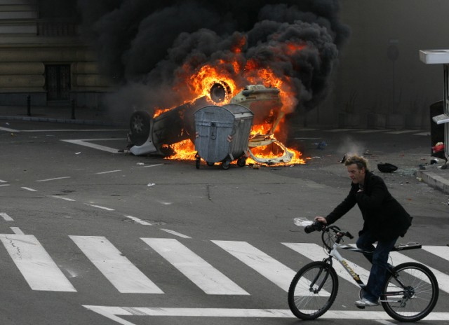 A man cycles past a burning police car during clashes between anti-gay protestors and Serbian riot police units in the center of Belgrade on October 10, 2010. Police clashed with hundreds of anti-gay protestors at Serbia's second ever Gay Pride march on October 10, with nearly 60 policemen and civilians reported wounded in the violence.  AFP PHOTO / MARKO DJOKOVIC