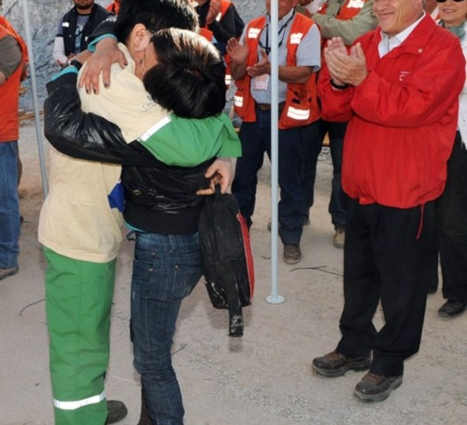 Handout picture released by Chile's presidential press office of Chilean President Sebastian Pinera (R) smiling as Chilean miner Carlos Bugueno (L) is hugged by his mother after being brought to the surface following a 10-week ordeal in the collapsed San Jose mine, near Copiapo, 800 km north of Santiago, Chile, on October 13, 2010.  A complex rescue of the 33 miners trapped more than two months in Chile sped towards its successful finale Wednesday, with just some of the men left to be winched to a world above awed and overjoyed by their improbable salvation.    AFP PHOTO/ALEX IBANEZ/PRESIDENCIA   RESTRICTED TO EDITORIAL USE   NO SALES FOR MARKETING