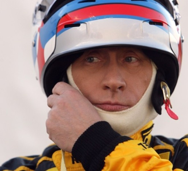 Russian Prime Minister Vladimir Putin puts on racing helmet as he wears the colours of the Renault Formula One team before driving a F1 race car on a special track in Leningrad region outside St. Petersburg on November 7, 2010.  AFP PHOTO / RIA NOVOSTI / POOL / ALEXEY DRUZHININ