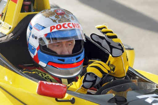 Russian Prime Minister Vladimir Putin wears a helmet and the uniform of the Renault Formula One team before driving a F1 race car on a special track in Leningrad region outside St. Petersburg on November 7, 2010.  AFP PHOTO / RIA NOVOSTI / POOL / ALEXEY DRUZHININ