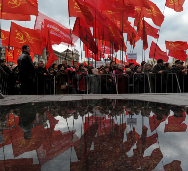 Activists of the Communist party are reflected on a puddle during a rally on Independence Square in Kiev on November 7, 2010. Several thousand supporters of Communist ideals marched to mark the overthrowing of the Romanov Dynasty by Bolshevik forces. AFP PHOTO/ SERGEI SUPINSKY
