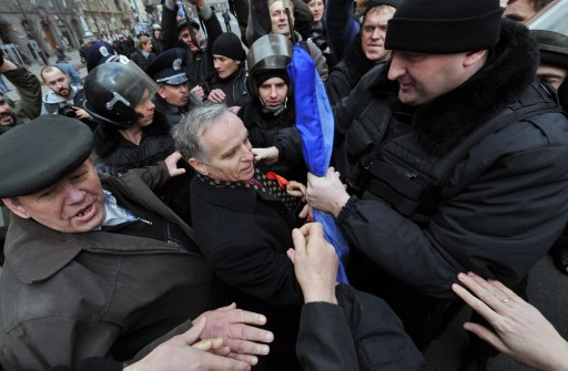 "Riot police arrest an anti-communmist during a march in Kiev on November 7, 2010. Supporters of Communist ideaology rallied today to mark Bolshevik Revolution Day, refered to as the ""Great October Socialist Revolution Day"" in the central of Ukrainian capital. AFP PHOTO/ SERGEI SUPINSKY"