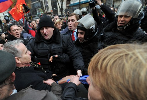 "Riot police apprehend anti-communmist protestors during a march in Kiev on November 7, 2010. Supporters of Communist ideaology rallied today to mark Bolshevik Revolution Day, refered to as the ""Great October Socialist Revolution Day"" in the central of Ukrainian capital. AFP PHOTO/ SERGEI SUPINSKY"