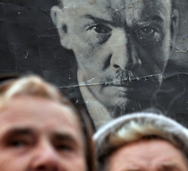 Activists of the Communist party stand in front of a poster of Lenin during a rally on Independence Square in Kiev on November 7, 2010. Several thousand supporters of Communist ideals marched to mark the overthrowing of the Romanov Dynasty by Bolshevik forces. AFP PHOTO/ SERGEI SUPINSKY