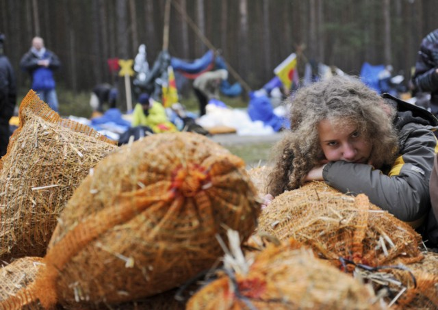 An anti nuclear protestor against the Castor transport and storage of nuclear waste rests on bags of hay at their  blockade after sleeping on the road leading to the storage facility in Gorleben, November 8, 2010. The northern German town of Gorleben will receive the contentious waste for storage among huge protests along the route from France to Germany.   AFP PHOTO/ODD ANDERSEN