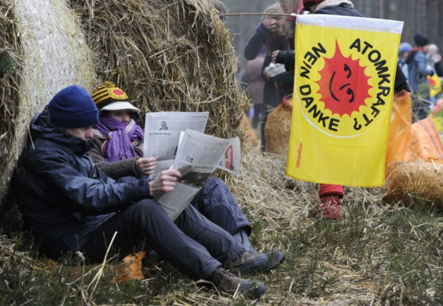 An anti nuclear protestor against the Castor transport and storage of nuclear waste rests on bags of hay at their  blockade after sleeping on the road leading to the storage facility in Gorleben, November 8, 2010. The northern German town of Gorleben will receive the contentious waste for storage among huge protests along the route from France to Germany.   AFP PHOTO/ODD ANDERSEN , Anti nuclear protestors against the transport and storage of nuclear waste reads the papers as they wake up at their blockade after sleeping on the road leading to the storage facility in Gorleben, November 8, 2010. The northern German town of Gorleben will receive the contentious waste for storage among huge protests along the route from France to Germany.   AFP PHOTO/ODD ANDERSEN