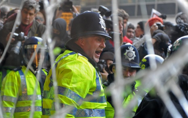 TOPSHOTS A police officer, pictured through a broken window, shouts at demonstrators as they clash with police at 30 Millbank, during a student protest march, in central London on November 10, 2010.   University students protesting against the British government's plans to triple tuition fees forced their way into the headquarters of Prime Minister David Cameron's party on Wednesday.  In chaotic scenes, around 20 students got into the lobby of Millbank, a 1960s office building near the Houses of Parliament that houses the Conservative Party, an AFP reporter said.      AFP PHOTO / BEN STANSALL