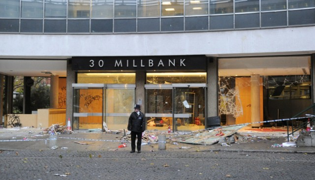 "A police officer guards the damaged entrance to 30 Millbank, a building housing the headquarters of the British Conservative Party, in London, on November 11, 2010. British Prime Minister David Cameron condemned as ""completely unacceptable"" Thursday the actions of students who stormed his party's London headquarters in protest over plans to increase tuition fees. Fourteen people were injured and about 35 arrested after thousands of demonstrators besieged the 1960s office building near parliament, smashing their way through the glass frontage and wrecking the lobby. AFP PHOTO/CARL COURT"