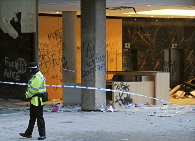 "A police officer guards the damaged entrance to 30 Millbank, a building housing the headquarters of the British Conservative Party, in London, on November 11, 2010. British Prime Minister David Cameron condemned as ""completely unacceptable"" Thursday the actions of students who stormed his party's London headquarters in protest over plans to increase tuition fees. Fourteen people were injured and about 35 arrested after thousands of demonstrators besieged the 1960s office building near parliament, smashing their way through the glass frontage and wrecking the lobby. AFP PHOTO/CARL COURT , A British police community support officer stands guard besides damage and graffiti left by protestors at 30 Millbank, a building housing the headquarters of the British Conservative Party, in London, on November 11, 2010. British Prime Minister David Cameron condemned as ""completely unacceptable"" Thursday the actions of students who stormed his party's London headquarters in protest over plans to increase tuition fees. Fourteen people were injured and about 35 arrested after thousands of demonstrators besieged the 1960s office building near parliament, smashing their way through the glass frontage and wrecking the lobby. AFP PHOTO/CARL COURT"