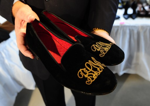 A pair of slippers belonging to Bernie Madoff, embroidered with his BLM initials in gold, are displayed during a press preview of Madoff auction items at the Brooklyn Navy Yard, November 10, 2010. Hundreds of items once belonging to Madoff will be auctioned off on November 13, 2010, running the gamut from a massive emerald-cut diamond to his black bedroom slippers, US officials said. Proceeds from the auction will compensate the victims of his multibillion USD Ponzi scheme. AFP PHOTO/Emmanuel Dunand