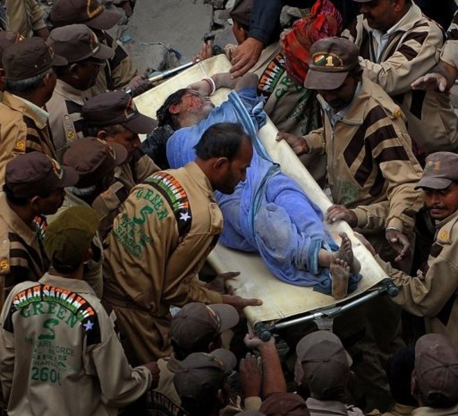 Rescue workers carry a body of a dead woman from the rubble in eastern New Delhi on November 16, 2010 after a building collapsed late November 15. At least 60 people died when the four-storey building in a crowded area of New Delhi collapsed, officials said, as rescuers hunted for more victims trapped in the rubble.    AFP PHOTO / MANAN VATSYAYANA