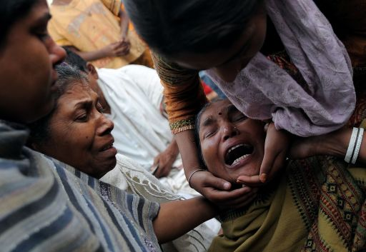 Relatives console an Indian woman (2R) who lost her grandchild in eastern New Delhi on November 16, 2010 after a building collapsed late on November 15. At least 60 people died when the four-storey building in a crowded area of New Delhi collapsed, officials said, as rescuers hunted for more victims trapped in the rubble.    AFP PHOTO/ MANAN VATSYAYANA