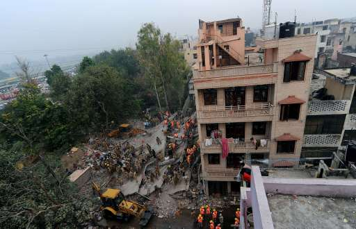 Relief workers carry out rescue operations amidst the rubble in eastern New Delhi on November 16, 2010 after a building collapsed late on November 15. At least 60 people died when the four-storey building in a crowded area of New Delhi collapsed, officials said, as rescuers hunted for more victims trapped in the rubble.    AFP PHOTO/ MANAN VATSYAYANA