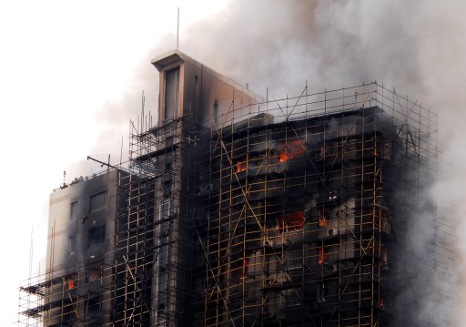 This photo taken on November 15, 2010 shows a huge fire engulfing a high-rise in Shanghai, after construction scaffolding surrounding the building initially caught fire, spreading to the building itself. The accident left at least five people dead, sending billowing plumes of black smoke over the city, state media and officials said.   CHINA OUT   AFP PHOTO