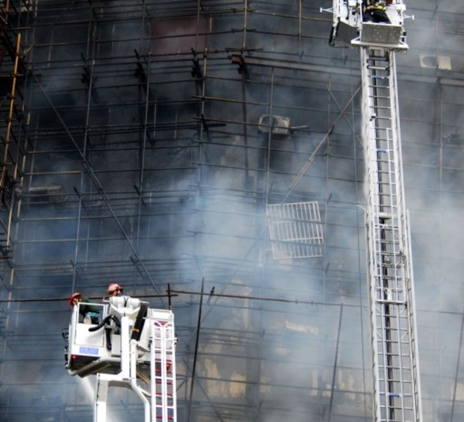 This photo taken on November 15, 2010 shows Chinese firefighters trying to extinguish a huge fire which engulfed a high-rise in Shanghai, after construction scaffolding surrounding the building initially caught fire, spreading to the building itself. The accident left at least five people dead, sending billowing plumes of black smoke over the city, state media and officials said.   CHINA OUT   AFP PHOTO