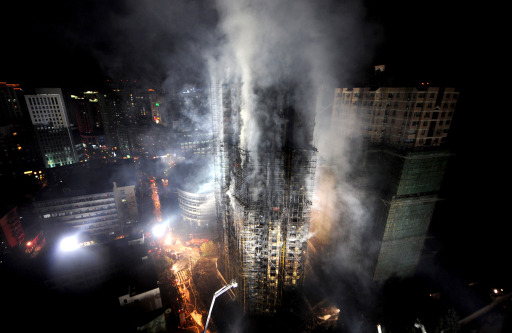 In this picture taken on November 15, 2010, Chinese firefighters extinguish a huge fire which engulfed a high-rise building in Shanghai, after construction scaffolding surrounding the building initially caught fire, spreading to the building itself. Shanghai residents voiced anger on November 16 over a high-rise fire that killed at least 53 people in the latest deadly incident to raise concern over lax safety standards in China.   CHINA OUT AFP PHOTO
