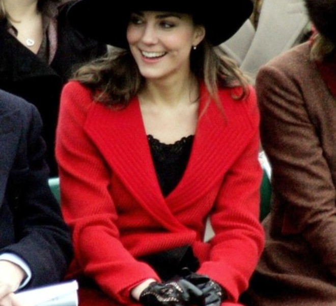 Kate Middleton sits in the stands as her boyfriend Britain's Prince William takes part in the Sovereign's Parade at The Royal Military Academy in Camberley, 35 miles west of London, 15 December 2006. Prince William graduated as an army officer with a royal display of parade-ground skills Friday, in a traditional military rite of passage for the second in line to Britain's throne. In a black uniform completed with a red sash and clutching a gleaming assault rifle, 24-year-old William joined 227 fellow cadets in the passing-out ceremony at Britain's elite Sandhurst army academy southwest of London. His girlfriend Kate Middleton looked on beaming at the faultless display, attended by his grandmother Queen Elizabeth II and the rest of the royal family. (Photo credit should read TIM OCKENDEN/AFP/Getty Images)