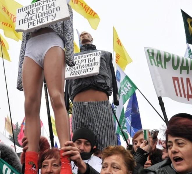 "Protesters shout slogans as they hold half-naked dummys with placard reading ""Small business owner-is victim of the new tax code"" during a many-thousands rally in front of Ukraine's parliament in Kiev on November 16, 2010. Ukrainian small and medium-sized enterprise owners protested against tax reform debating by the parliament. AFP PHOTO/ SERGEI SUPINSKY"