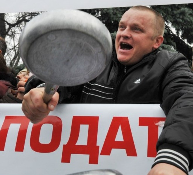 A protester shouts slogans as he beats frying pans together on November 16, 2010 during a rally in front of the Ukrainian Parliament in Kiev. Ukrainian small and medium-size enterprise owners protested against a tax reform bill being debated at the parliament. AFP PHOTO/ SERGEI SUPINSKY