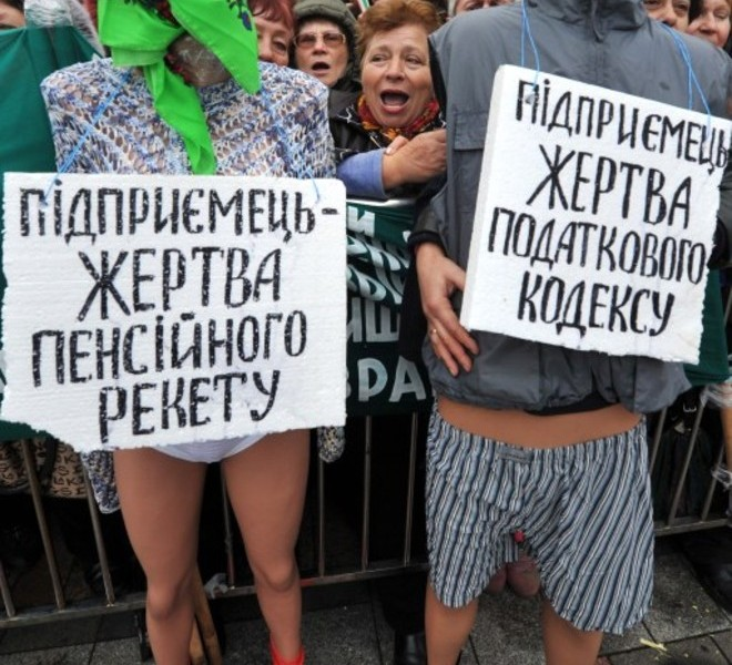 "Protesters shout slogans behind half-naked dummys with placard reading ""Small business owner- is victim of the new tax code"" during a many-thousands rally in front of Ukraine's parliament in Kiev on November 16, 2010.  Ukrainian small and medium-sized enterprise owners protested against tax reform debating by the parliament. AFP PHOTO/ SERGEI SUPINSKY"